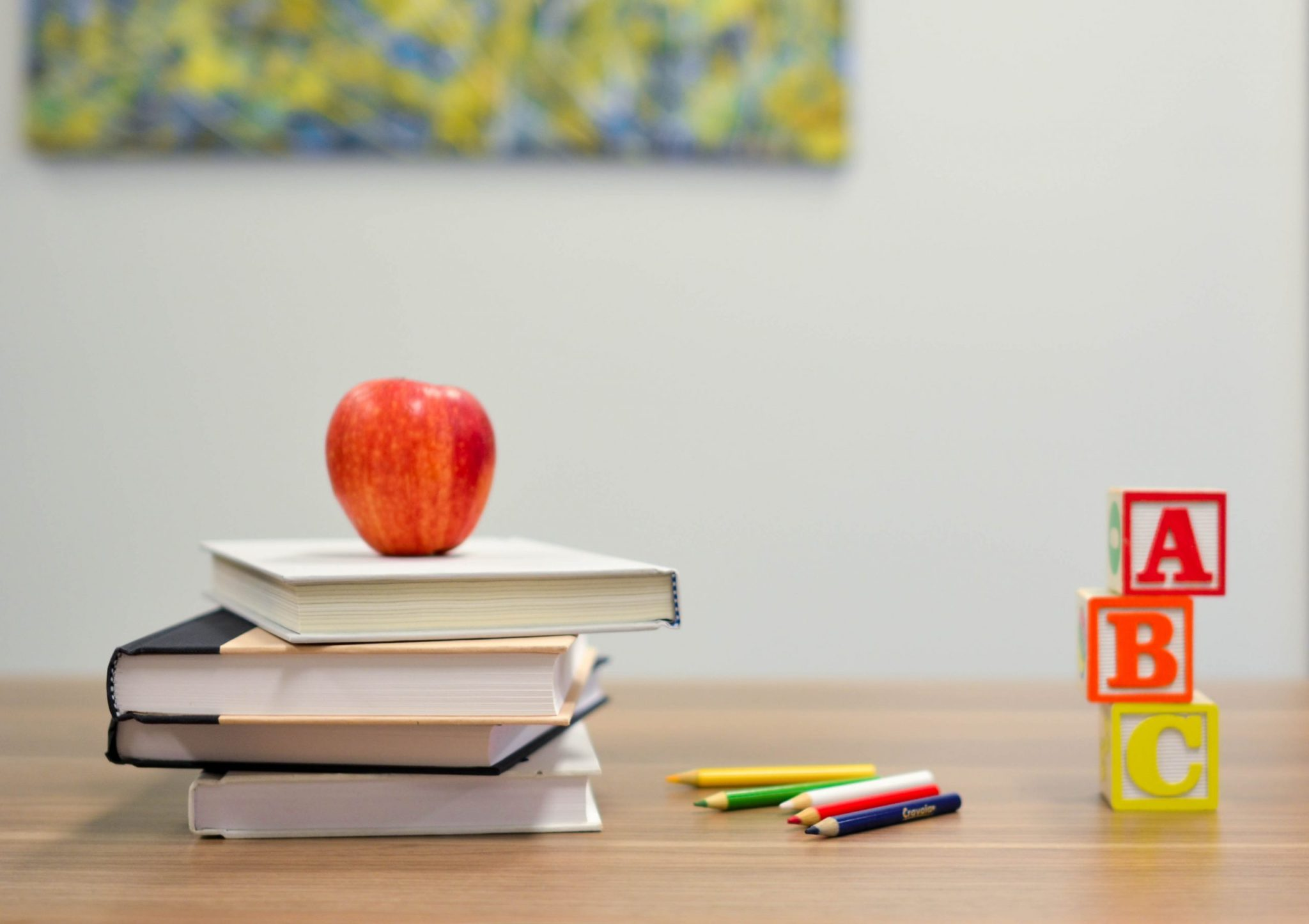 red apple fruit on four pyle books