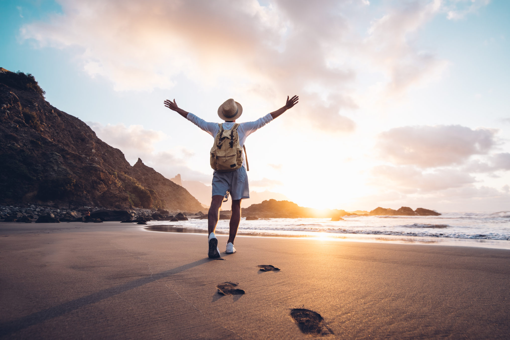 young,man,arms,outstretched,by,the,sea,at,sunrise,enjoying