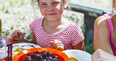 girl in red and white striped shirt holding white ceramic bowl with red and black fruits