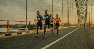 four men running on asphalt floor